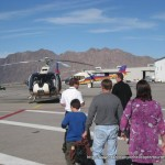 Travelers walking the tarmac to their EcoStar 130 helicopter.